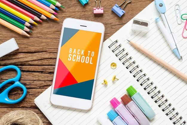 Maquette de téléphone portable avec des articles de papeterie scolaire sur bois de grunge