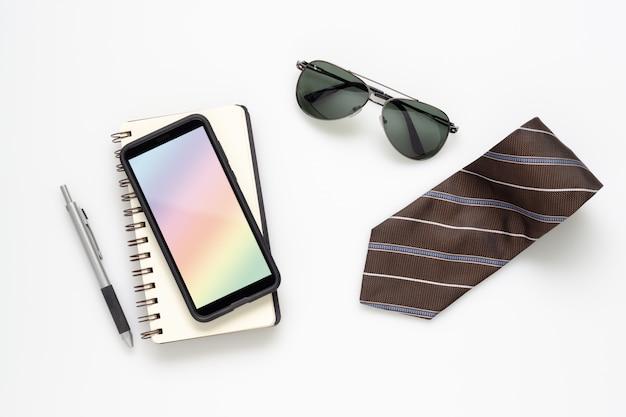 Maquette de téléphone portable smartphone avec accessoires gentleman sur la table de bureau blanche.