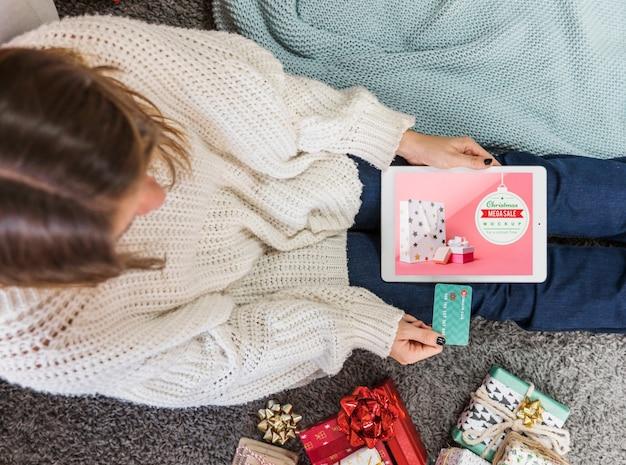 Maquette de vente de noël avec une femme à l'aide d'un ordinateur portable