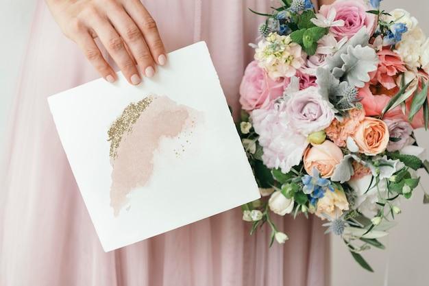 Mariée tenant une maquette de carte avec un bouquet de fleurs
