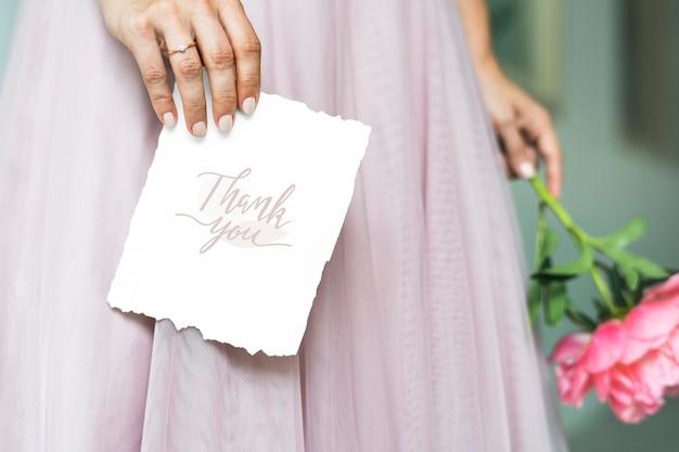 Mariée tenant une maquette de carte de remerciement