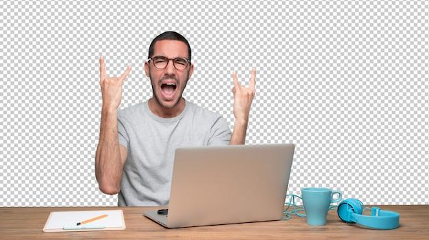 Méchant jeune homme assis à son bureau et faisant un geste de roche