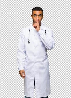 Médecin jeune afro-américain montrant un geste du silence mettant le doigt dans la bouche