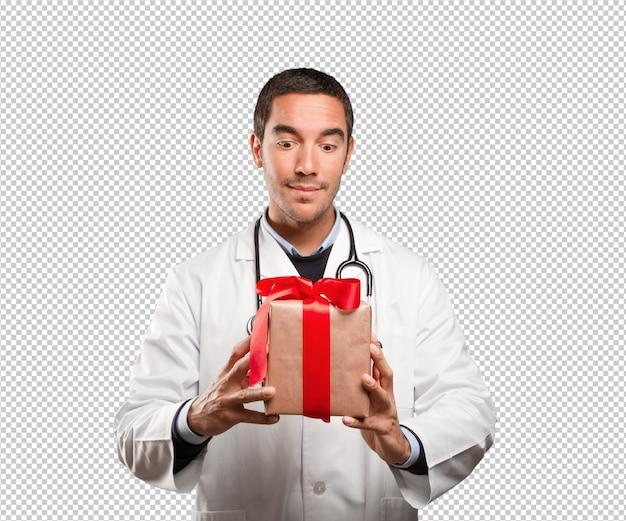 Médecin surpris tenant un cadeau sur fond blanc