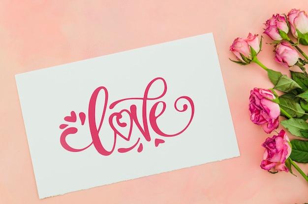 Message de feuille d'amour avec des fleurs à côté