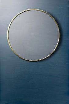 Miroir encadré d'or sur une maquette de mur bleu