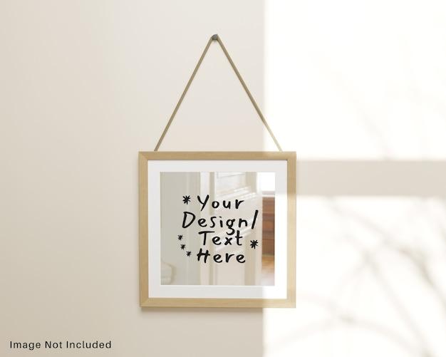 Miroir à réflexion carré avec cadre en bois suspendu à une maquette murale