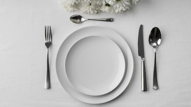 Mise à plat des assiettes sur la table avec des couverts et des fleurs