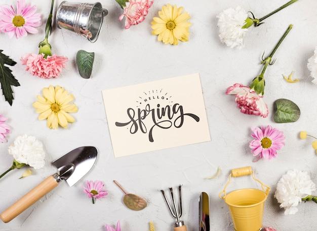 Mise à plat d'assortiment de fleurs de printemps et d'outils de jardinage