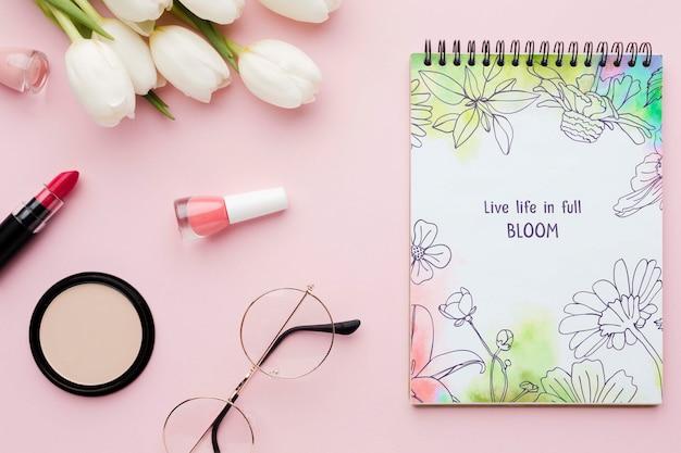 Mise à plat de cahier avec des tulipes et des essentiels de maquillage