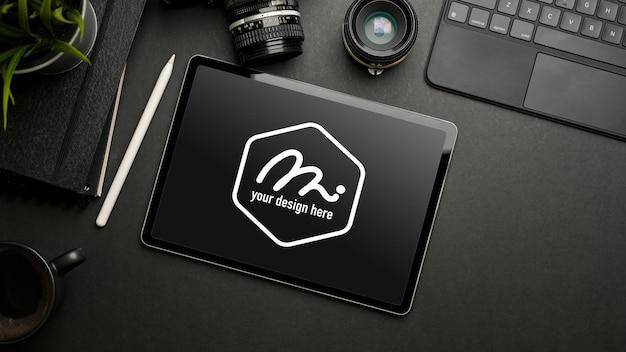 Mise à plat créative sombre avec maquette de tablette numérique, appareil photo, articles de papeterie et accessoires, vue de dessus