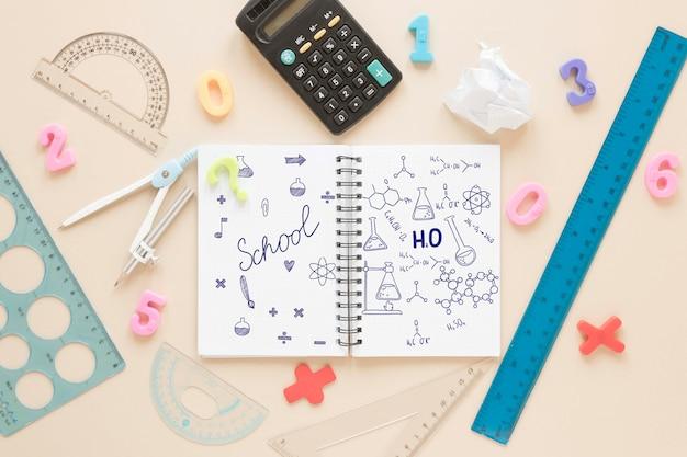 Mise à plat du cahier avec calculatrice et règles
