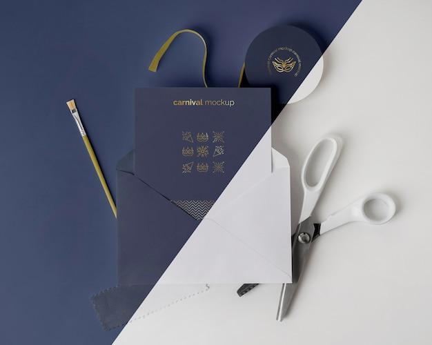 Mise à plat d'invitation de carnaval dans une enveloppe avec des ciseaux et un pinceau