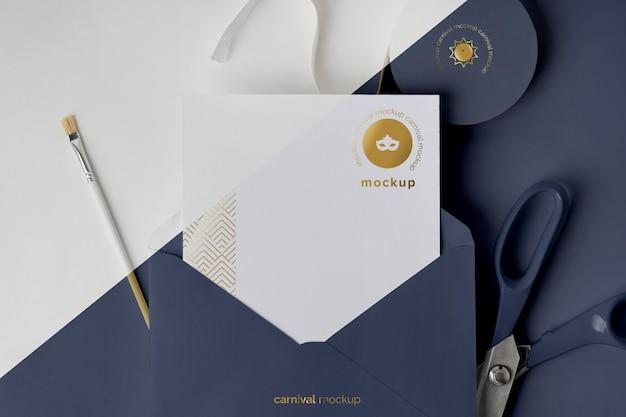 Mise à plat de l'invitation de carnaval dans une enveloppe avec du ruban adhésif et des ciseaux