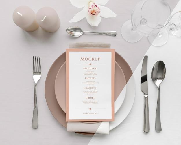 Mise à plat de la maquette du menu de printemps sur des assiettes avec des bougies et des couverts