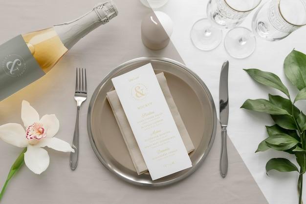 Mise à plat de la maquette du menu de printemps sur des assiettes avec une bouteille de vin et des couverts