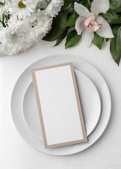 Mise à plat d'une maquette de menu de printemps avec assiettes et fleurs