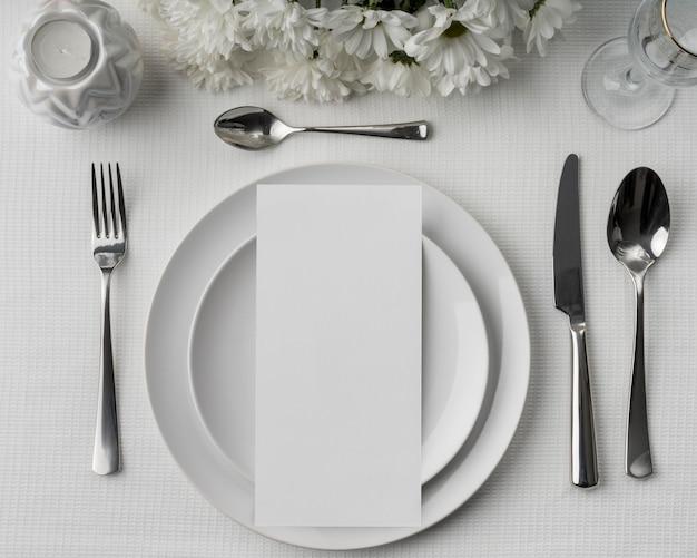 Mise à plat de la maquette de menu de printemps avec des fleurs et des couverts sur des assiettes