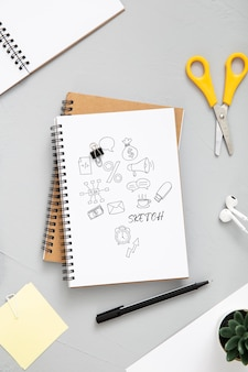 Mise à plat de la surface du bureau avec des ciseaux et un bloc-notes