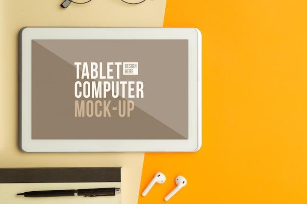 Mise à plat, vue de dessus du bureau de table de bureau orange avec maquette d'ordinateur tablette
