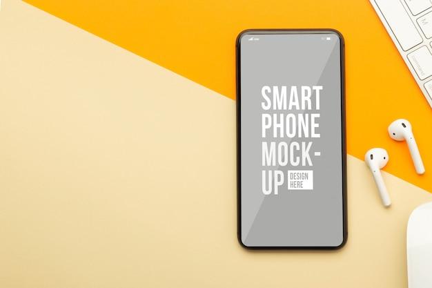 Mise à plat, vue de dessus du bureau de table de bureau orange avec modèle de maquette d'écran de smartphone pour votre conception