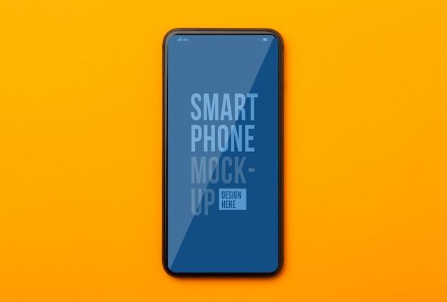 Mise à plat, vue de dessus du bureau de table de bureau orange avec modèle de maquette de smartphone pour votre conception.
