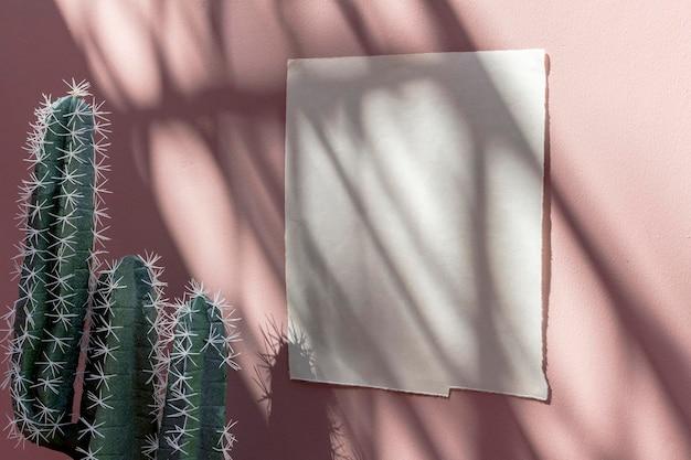Modèle d'affiche blanche sur un mur rose pastel par des cactus