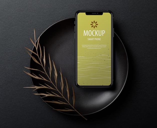 Modèle de maquette d'écran iphone avec des feuilles sèches