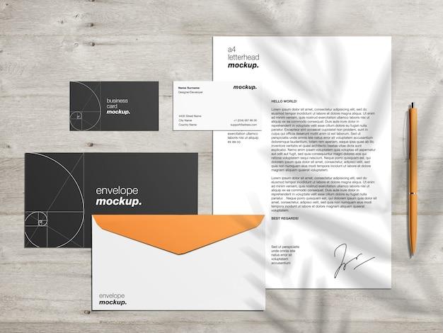 Modèle de maquette d'identité de marque professionnelle avec papier à en-tête, enveloppes et cartes de visite sur un bureau en bois