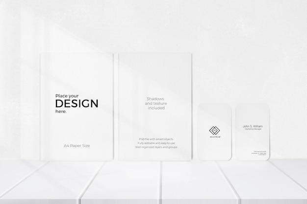 Modèle Modifiable De Feuilles Et De Cartes De Visite Devant Un Mur Blanc Psd gratuit