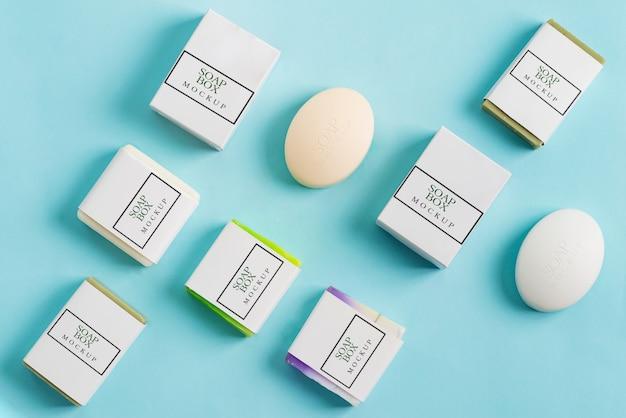 Modèle de spa de barre de savon naturel fait à la main et de boîtes d'artisanat en papier maquette pour l'emballage sur un fond bleu clair.