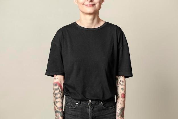 Modèle avec tatouage en maquette de t-shirt noir