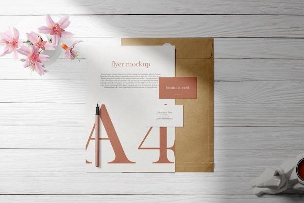 Nettoyer une carte de visite minimale et une maquette a4 sur une enveloppe avec un vase et un stylo