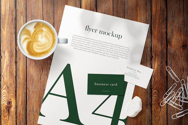 Nettoyer une maquette de carte de visite minimale et du papier a4 sur une table en bois supérieure avec une tasse à café et des clips