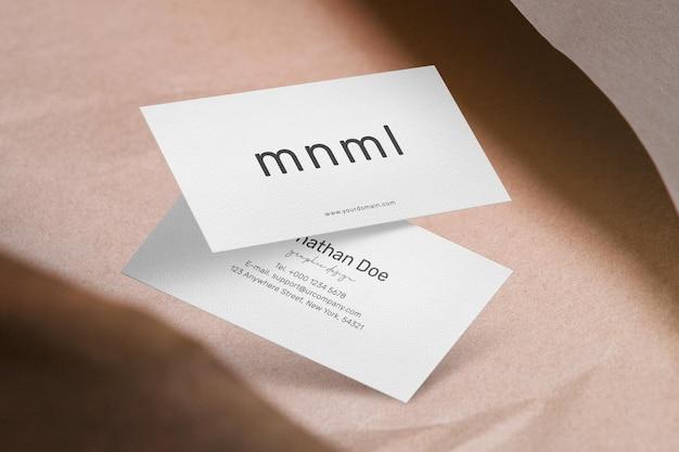 Nettoyer une maquette de carte de visite minimale sur du papier kraft avec une ombre.