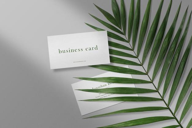 Nettoyer la maquette de carte de visite minimale sur les feuilles avec ombre et lumière