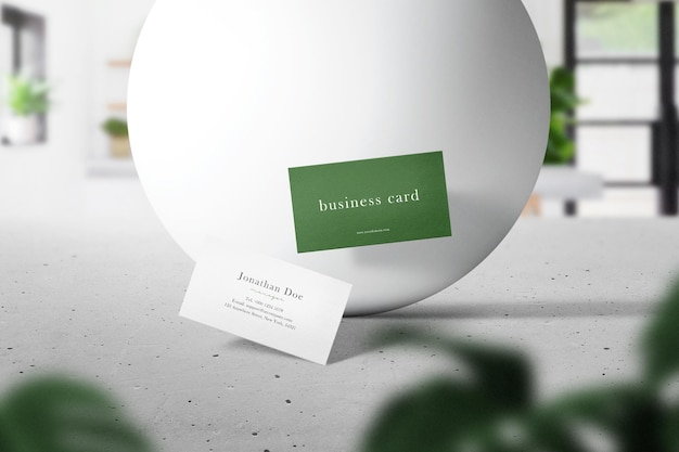 Nettoyer une maquette de carte de visite minimale flottant sur le ciment supérieur avec une sphère