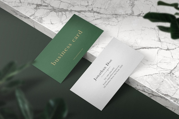 Nettoyer la maquette de carte de visite minimale sur une plaque de marbre avec des feuilles