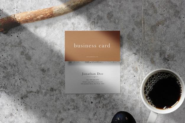 Nettoyer Une Maquette De Carte De Visite Minimale Sur Un Sol En Béton Avec Une Tasse à Café PSD Premium