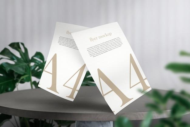 Nettoyez la maquette minimale de document a4 sur une table en pierre avec des feuilles vertes.