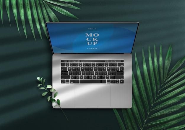 Notebook pro mockup vue de dessus sur une zone verte avec des feuilles