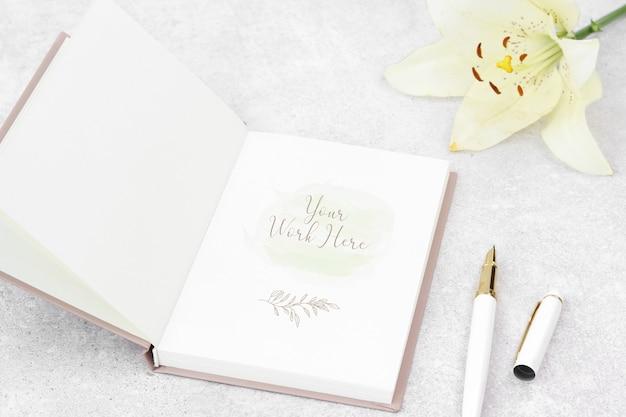 Notes de maquette avec lys et stylo blanc