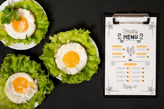 Oeufs sur salade avec menu du matin au restaurant