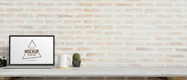 Ordinateur portable avec écran de maquette sur un bureau en marbre avec appareil photo et décorations avec mur de briques