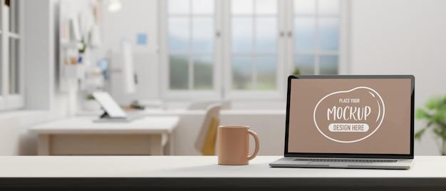 Ordinateur portable avec écran de maquette et tasse de café sur la table dans une salle de bureau confortable rendu 3d