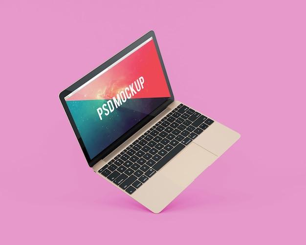 L'ordinateur portable sur fond rose se moque