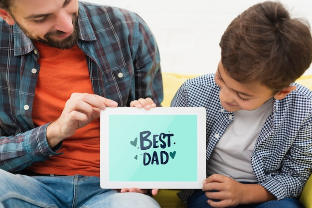 Papa et fils tenant une tablette électronique