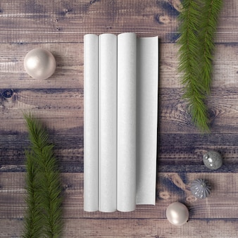 Papier blanc sur table en bois entouré de boules et de pins