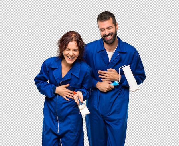 Des peintres souriants en mettant les mains sur la poitrine
