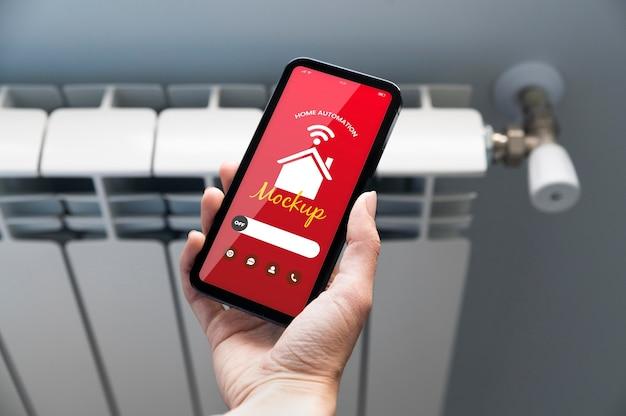 Personne tenant un smartphone avec une application domotique